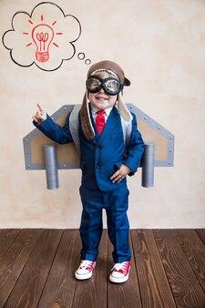 Retrato de joven empresario con alas de papel de juguete.