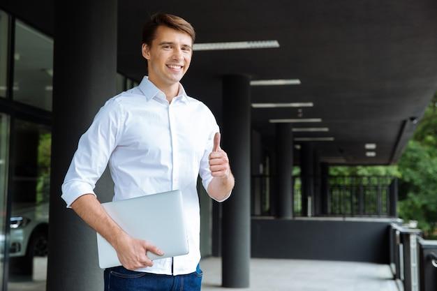 Retrato de joven empresario alegre cerca del centro de negocios