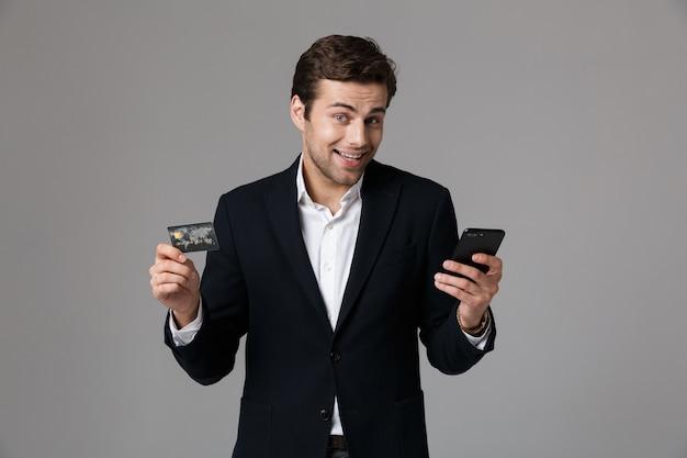 Retrato de un joven empresario alegre vestido con traje aislado sobre pared gris, mediante teléfono móvil, mostrando la tarjeta de crédito