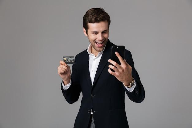 Retrato de un joven empresario alegre vestido con traje aislado sobre una pared gris, mediante teléfono móvil, mostrando la tarjeta de crédito