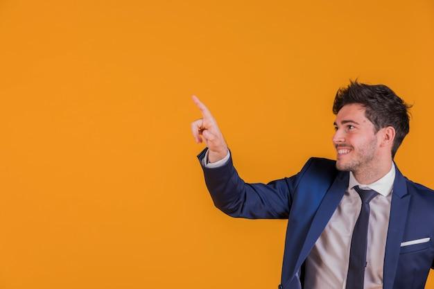 Retrato de un joven empresario apuntando su dedo contra un telón de fondo naranja