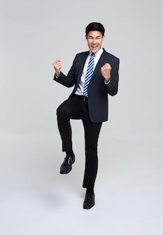 Retrato de joven empresario asiático feliz y exitoso en estudio blanco.