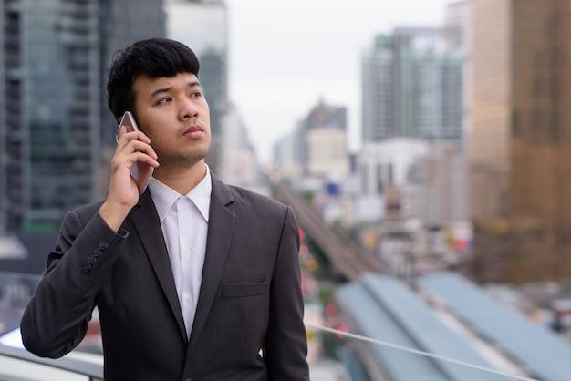 Retrato de joven empresario asiático con teléfono contra la vista de la ciudad