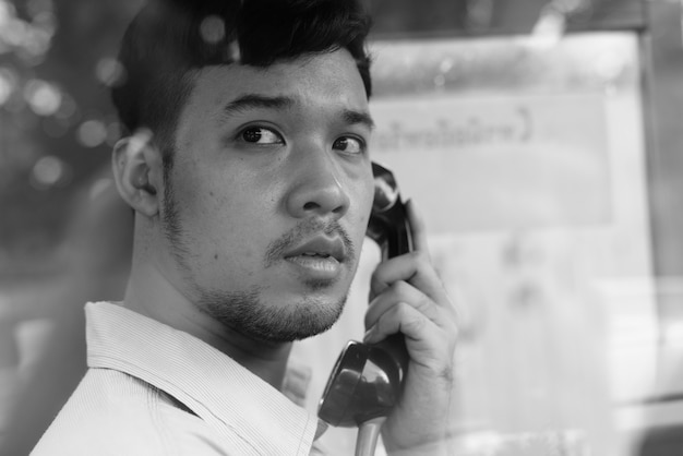 Retrato de joven empresario asiático utilizando el teléfono público al aire libre