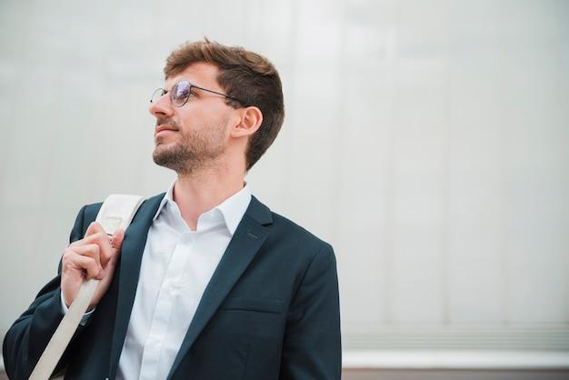 Retrato de un joven empresario con bolsa en su hombro