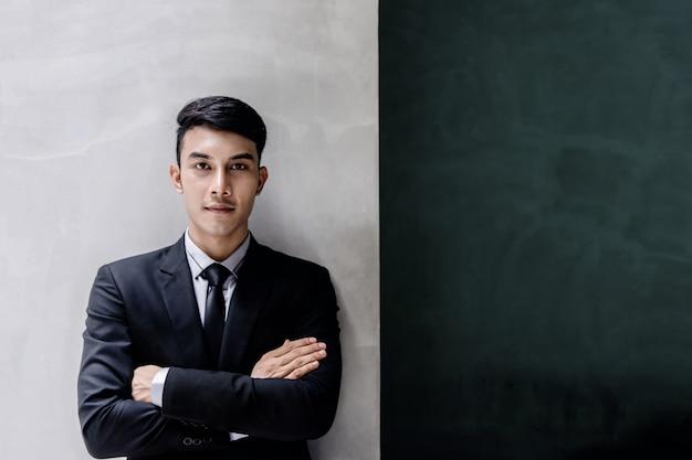 Retrato de joven empresario confía en traje formal negro.
