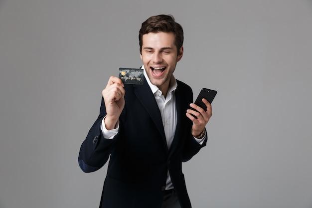 Retrato de un joven empresario emocionado vestido con traje aislado sobre pared gris, mediante teléfono móvil, mostrando la tarjeta de crédito