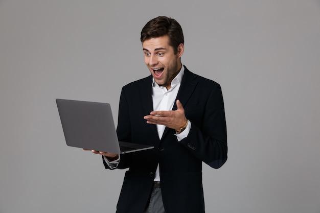 Retrato de un joven empresario emocionado vestido con traje aislado sobre pared gris, utilizando equipo portátil