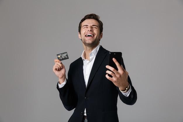 Retrato de un joven empresario encantado vestido con traje aislado sobre pared gris, mediante teléfono móvil, mostrando la tarjeta de crédito