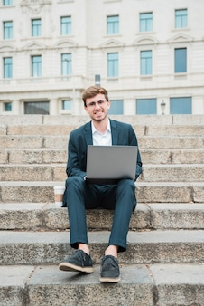 Retrato de un joven empresario exitoso sentado en la escalera con la computadora portátil