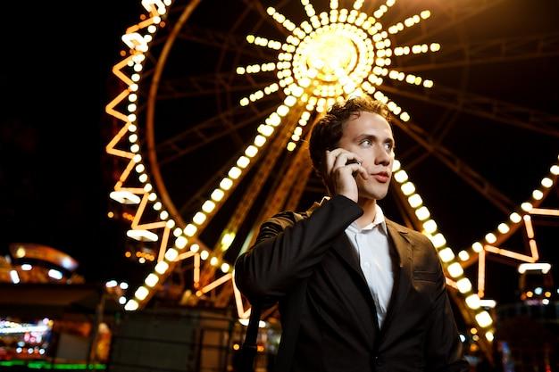Retrato de joven empresario exitoso sobre el parque de atracciones nocturno. dof superficial