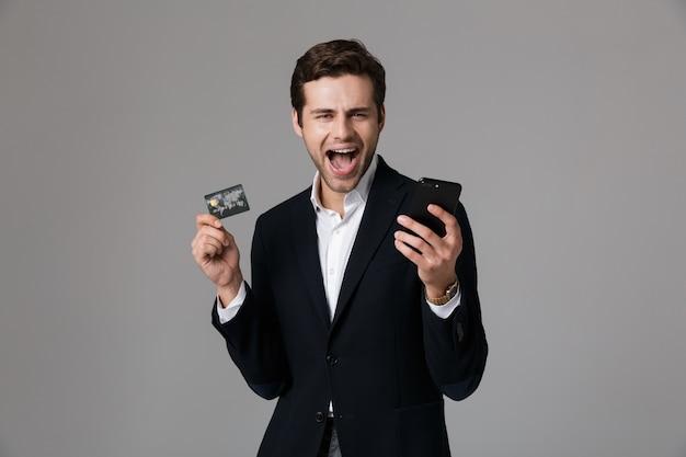 Retrato de un joven empresario feliz vestido con traje aislado sobre pared gris, mediante teléfono móvil, mostrando la tarjeta de crédito