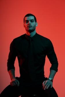 Retrato de un joven empresario guapo confía en luz azul y roja