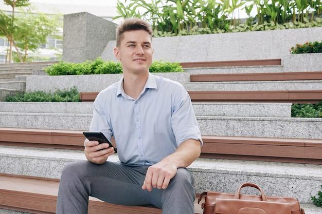 Retrato de joven empresario guapo emocionado con smartphone en manos sentado en un banco y mirando a otro lado