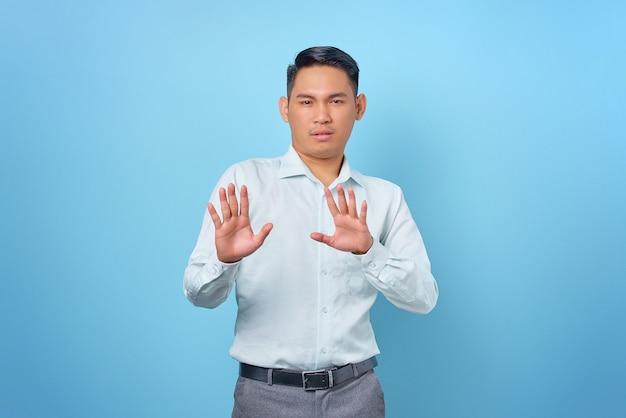 Retrato de joven empresario guapo enojado haciendo gesto de parada con las palmas de las manos sobre fondo azul.