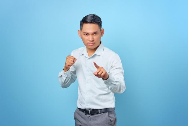 Retrato de joven empresario guapo enojado haciendo señal de advertencia sobre fondo azul.
