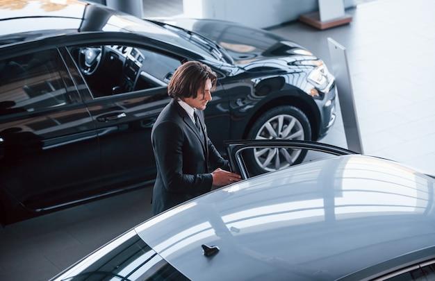 Retrato de joven empresario guapo en traje negro y corbata en el interior cerca de coche moderno.