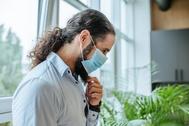 Retrato de joven empresario en máscara médica protectora en la oficina