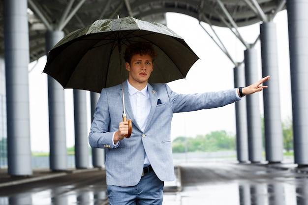 Retrato de joven empresario pelirrojo coger el coche y sosteniendo el paraguas