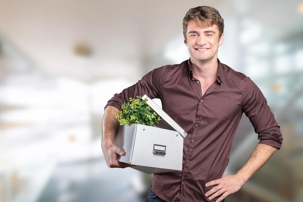 Retrato de joven empresario con planta en caja de cartón