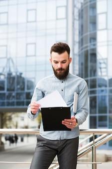 Retrato de un joven empresario revisando el documento frente al edificio de oficinas