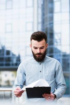 Retrato de un joven empresario revisando el documento en el portapapeles frente al edificio de oficinas