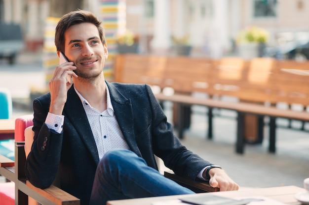 Retrato de joven empresario sonriente hablando por teléfono