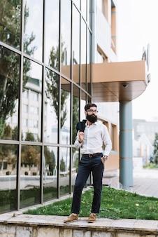 Retrato de joven empresario sosteniendo abrigo sobre su hombro de pie cerca del edificio corporativo