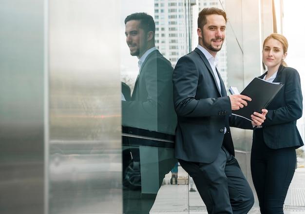 Retrato de un joven empresario sosteniendo una carpeta en la mano de pie con el colega de su hembra al aire libre