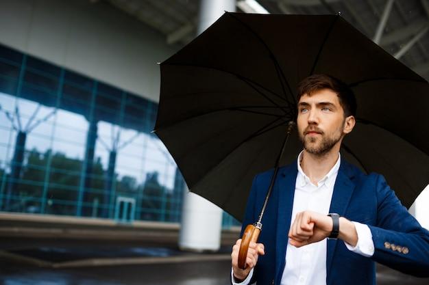 Retrato de joven empresario sosteniendo paraguas y mirando el reloj esperando