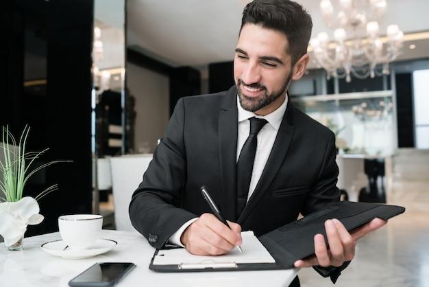 Retrato de joven empresario trabajando en el vestíbulo del hotel. concepto de viajes de negocios.