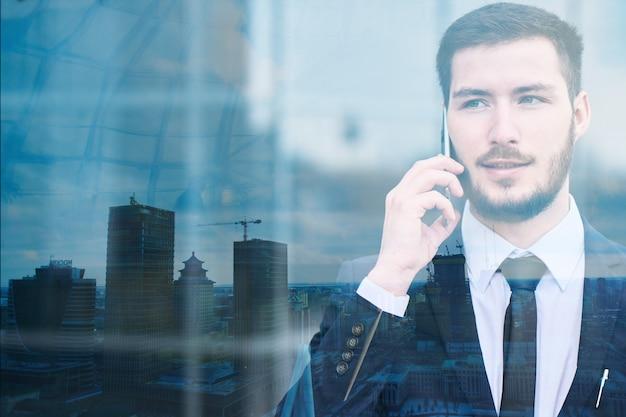 Retrato de un joven empresario en un traje azul hablando por un teléfono celular