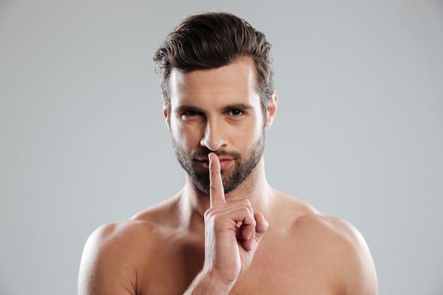 Retrato de un joven encantador hombre desnudo que muestra gesto de silencio