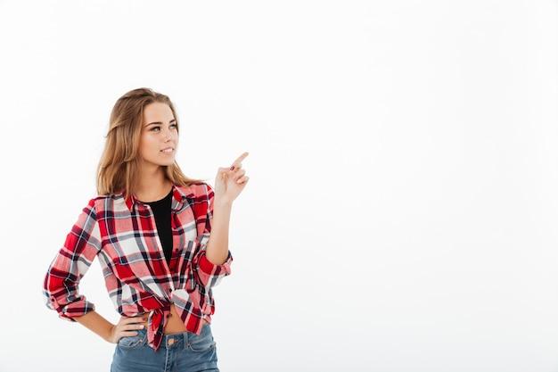 Retrato de una joven encantadora en camisa a cuadros de pie