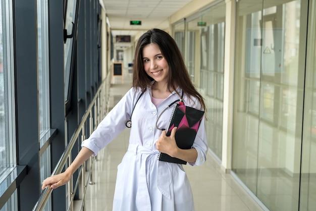 Retrato de joven enfermera en un instituto médico con estetoscopio. espacio publicitario