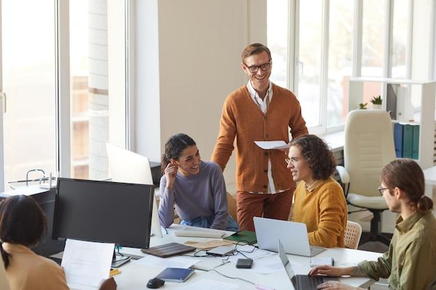 Retrato de joven equipo de desarrollo de ti discutiendo el proyecto y sonriendo mientras disfruta del trabajo en la oficina de producción de software, espacio de copia