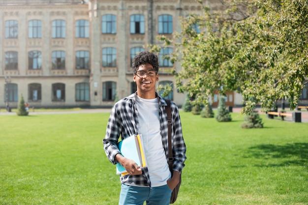 Retrato de un joven estudiante afroamericano hombre negro el fondo de la universidad.