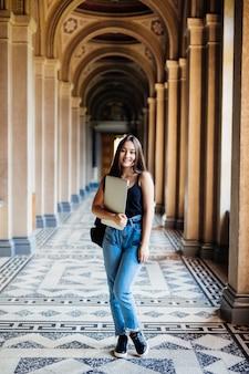 Retrato de joven estudiante asiática usando una computadora portátil o tableta en pose inteligente y feliz en la universidad o colegio,