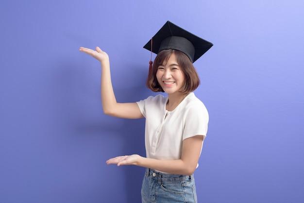 Un retrato de joven estudiante asiático con gorro de graduación sobre fondo de estudio.