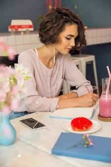 Retrato de una joven estudiante en auriculares escribiendo notas