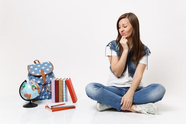Retrato de joven estudiante disgustado insatisfecho manteniendo la mano cerca de la cara sentada mirando en la mochila del globo, libros escolares aislados