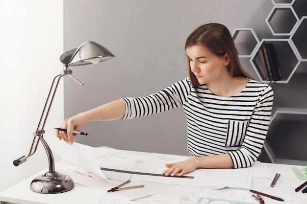Retrato de joven estudiante morena con el pelo largo en camisa a rayas sentado a la mesa en casa, haciendo proyectos de arquitecto para los exámenes, mirando dibujos con expresión de la cara concentrada.