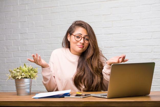 Retrato de joven estudiante mujer latina sentada en su escritorio dudando y encogiéndose de hombros
