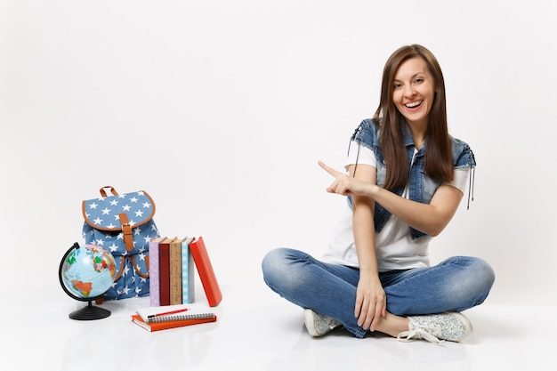 Retrato de joven estudiante mujer riendo casual en ropa de mezclilla sentado apuntando con el dedo índice en el mundo mochila libros escolares aislados