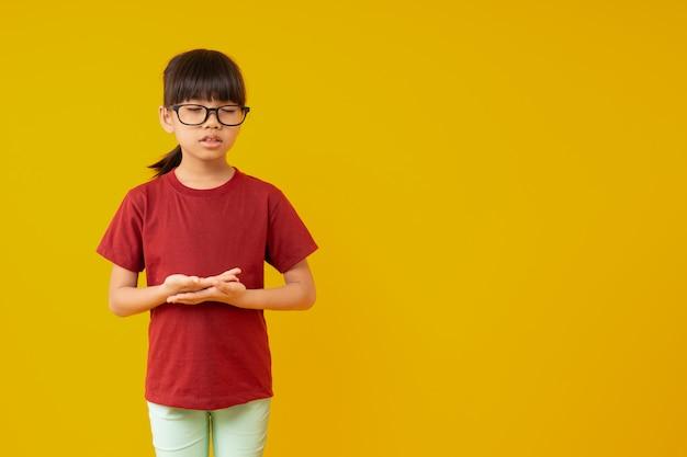Retrato de joven estudiante de niño asiático de pie y haciendo meditación