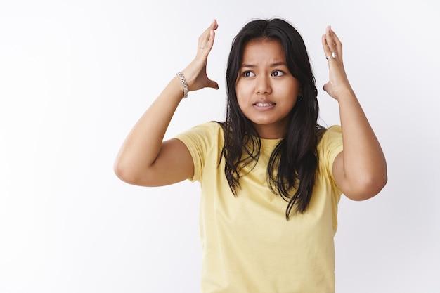 Retrato de joven estudiante preocupada y estresada bajo presión durante los exámenes y el trabajo dándose la mano alrededor de la cabeza y apretando los dientes angustiados, perplejos mirando nerviosamente a la izquierda sobre la pared blanca