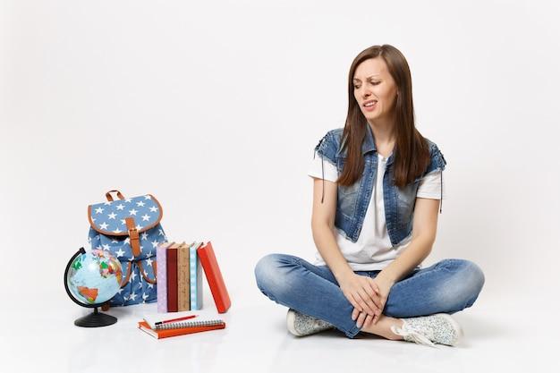 Retrato de joven estudiante preocupado desconcertado en ropa de mezclilla sentado y mirando en el mundo mochila libros escolares aislados