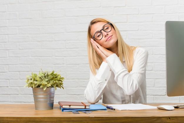 Retrato de joven estudiante sentada en su escritorio haciendo tareas cansadas y con mucho sueño