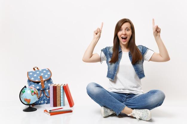 Retrato de joven estudiante sorprendida en ropa de mezclilla apuntando con el dedo índice hacia arriba sentado cerca del globo, mochila, libros escolares aislados