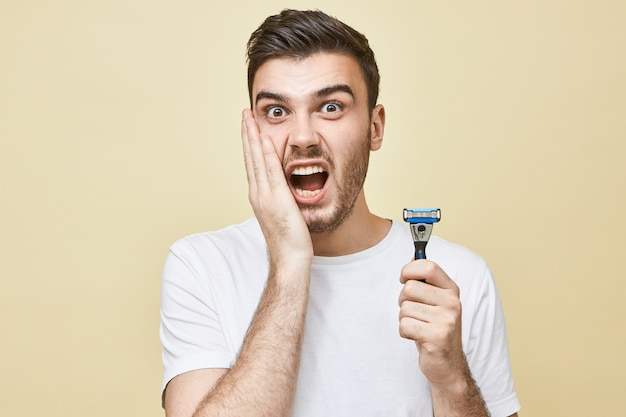 Retrato de un joven europeo frustrado e infeliz con barba que sostiene la mano en la mejilla y gritando, con mirada aterrorizada, que sufre de irritación de la piel debido al afeitado, sosteniendo una maquinilla de afeitar